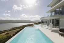 Sunny, tranquil modern luxury home showcase exterior with infinity pool and ocean view — Stock Photo
