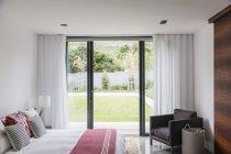 Quarto interior de casa vitrine com portas de pátio que conduzem ao pátio — Fotografia de Stock