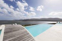 Sunny modern luxury infinity pool with footbridge and ocean view — Stock Photo