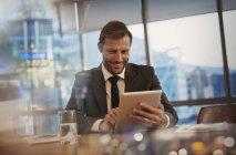 Улыбающийся бизнесмен, использующий цифровой планшет в конференц-зале — стоковое фото