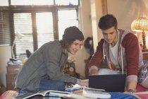 Jóvenes universitarios estudiantes usando laptop - foto de stock