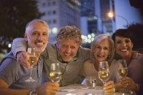 Портрет улыбающихся пар, пьющих белое вино в кафе на тротуаре — стоковое фото