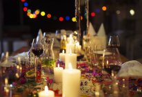 Lit candles on table at party — Stock Photo