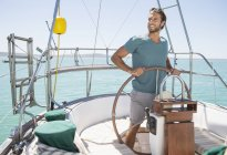Man steering sailboat on water — Stock Photo