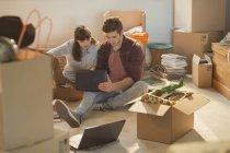 Junges Paar mit Laptop umgeben von Umzugskartons — Stockfoto