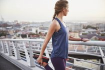 Женщины бегун, растяжение ноги на городской пешеходный мост — стоковое фото