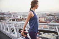 Läuferin streckt Bein auf städtischem Steg — Stockfoto