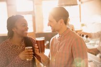 Smiling couple drinking beer in bar together — Stockfoto