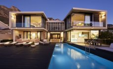 Modern luxury home showcase exterior and swimming pool illuminated at night — Stock Photo