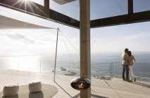 Couple standing on balcony of modern home — Stock Photo