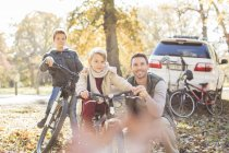 Portrait father and sons with bicycles in autumn park — Stock Photo