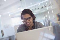 Smiling creative businessman working at laptop — Stock Photo