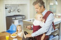 Father with baby packing bag for work — Stock Photo