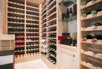 Garrafas de vinho organizadas em prateleiras na adega — Fotografia de Stock