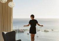 Woman standing at balcony railing overlooking ocean — Stock Photo