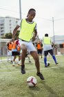 Soccer player training tricks on city field — Stock Photo