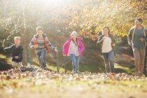 Família correndo no parque com folhas de outono — Fotografia de Stock