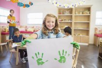 Student holding finger painting in class — Stock Photo