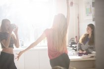 Teenage girls dancing and photographing in kitchen — Stock Photo