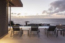 Lounge chairs on luxury patio with sunset ocean view — Stock Photo