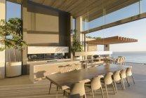 Солнечный современные, роскошные дома витрина интерьер обеденный стол с видом на океан — стоковое фото