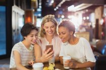 Young women friends using cell phone and drinking coffee in cafe — Stock Photo