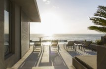Lounge chairs on sunny luxury patio with ocean view — Stock Photo