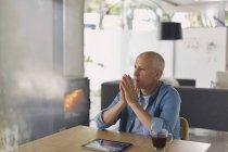 Homme pensif avec tablette numérique boire du café et à la recherche de suite près de poêle cheminée à bois — Photo de stock