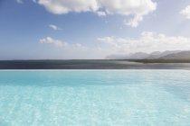 Soleggiata, tranquilla piscina a sfioro con vista sull'oceano sotto il cielo blu con nuvole — Foto stock