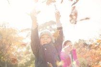 Entusiástico menino brincando em folhas de outono — Fotografia de Stock