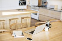 Laptop, French press coffee, cell phone and notebook on kitchen table — Stock Photo