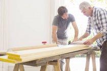 Vater und Sohn schauen sich Baupläne an — Stockfoto
