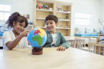 Students examining globe in classroom — Stock Photo