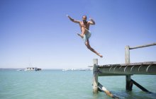 Couple jumping off wooden dock into water — Stock Photo