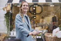 Retrato de mujer sonriente con compras de la ventana de bicicleta - foto de stock