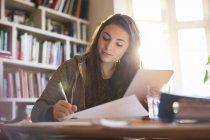 Teenager-Mädchen mit digitalem Tablet macht Hausaufgaben am Schreibtisch — Stockfoto