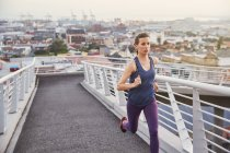 Läuferin läuft auf städtischer Fußgängerbrücke — Stockfoto