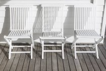 White folding chairs in a row on sunny patio — Stock Photo