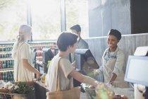 Улыбающиеся женщина кассир, помогая клиента на кассе супермаркета — стоковое фото