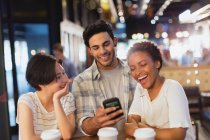 Young friends using cell phone, texting and laughing at cafe — Stock Photo