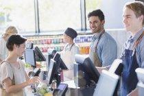 Portrait souriant, confiant jeune caissier masculin travaillant à l'épicerie caisse du marché — Photo de stock