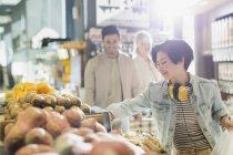 Young woman with headphones grocery shopping, browsing produce in market — Stock Photo