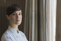 Portrait confident brunette woman at window — Stock Photo