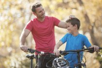 Père et fils affectueux avec des vélos de montagne à l'extérieur — Photo de stock
