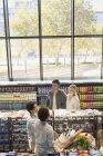 Junge Paare reden und Einkaufsmöglichkeiten im Markt — Stockfoto