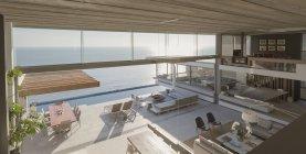 Повышенных мнение современные, роскошные дома витрина интерьер гостиной и патио с видом на океан Солнечный — стоковое фото