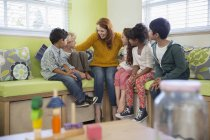 Students and teacher talking in classroom — Stock Photo