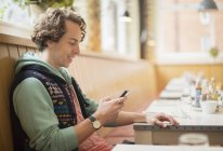 Happy young man using cell phone in cafe — Stock Photo