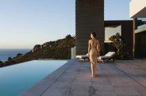Woman in dress walking along infinity pool overlooking ocean — Stock Photo