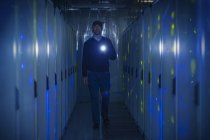 Server room technician with flashlight in dark corridor — Stock Photo